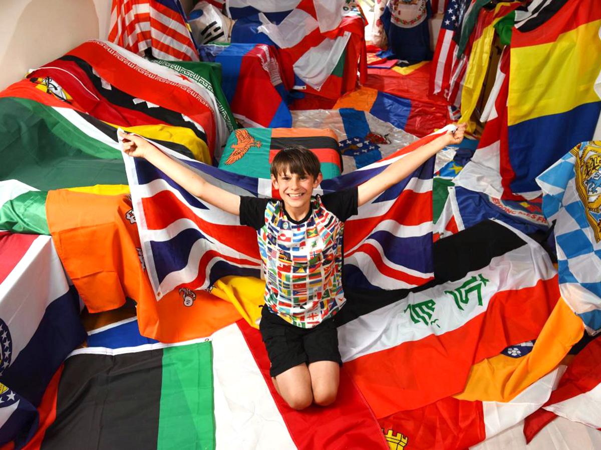 発達障害の少年は集めた世界中の国旗に囲まれ安心して生活できる